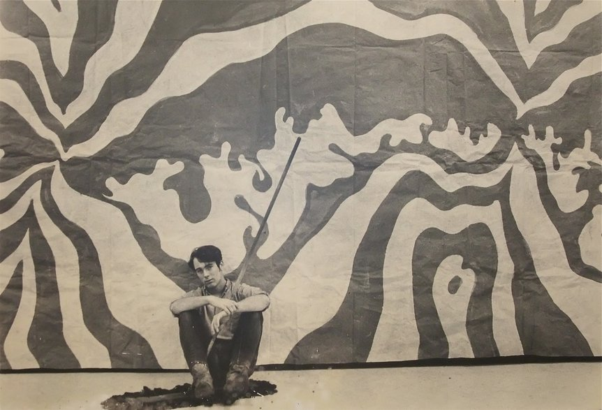 A young Gordon Carlisle in front of one of his first murals, ca. 1968 (Photo: Robert Carlisle)