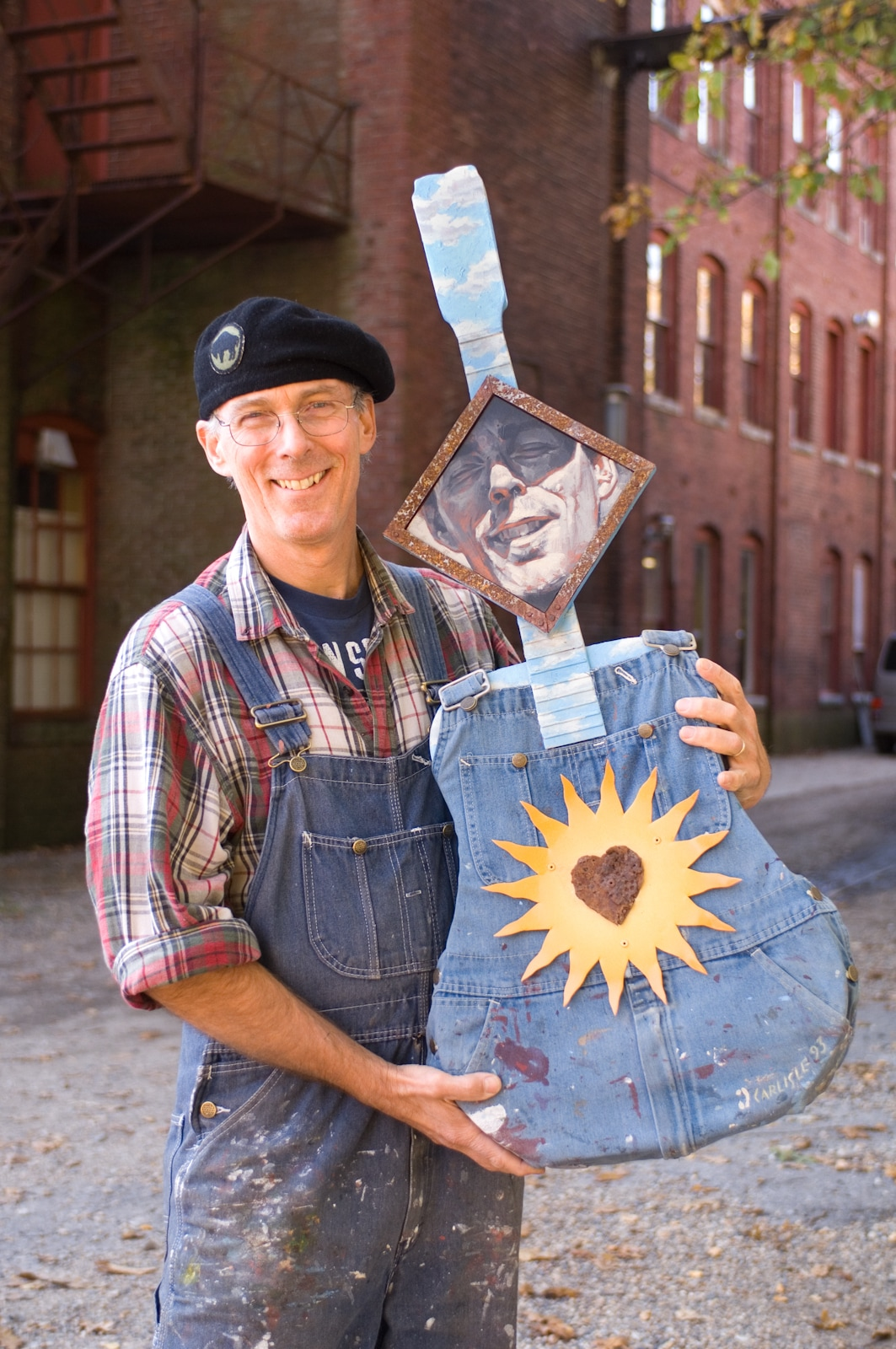 Artist with self portrait (mixed media; photo by Tim Gaudreau)